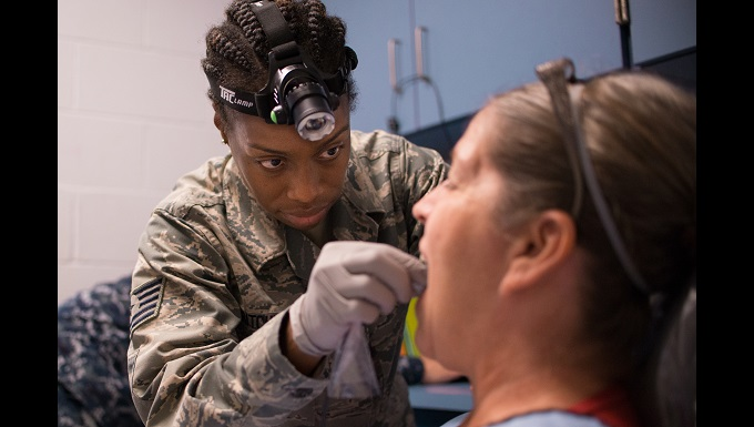 Tech. Sgt. Tambria Pritchett, a dental technician from the Texas Air National Guard's 136th Medical Group, inspects the teeth of a patient June 20, 2018, at one of four health-care clinics in Eastern Kentucky. Members of the Air National Guard and U.S. Navy Reserve are conducting Operation Bobcat, which provides military health-care troops with critical training in logistics and field operations while providing lasting benefits to the civilian community. The clinics offer no-cost medical screenings; dental cleanings, fillings and extractions; vision exams and no-cost eyeglasses. (U.S. Air National Guard photo by Tech. Sgt. Lynn Means)